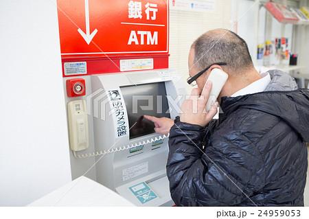 ATMの備え付け受話器で話す中年男性 24959053