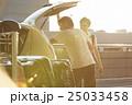 空港の駐車場で車に荷物を積み込男性 25033458
