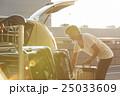 空港の駐車場で車に荷物を積み込男性 25033609