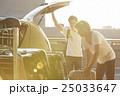 空港の駐車場で車に荷物を積み込男性 25033647