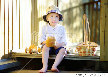 Little boy in straw hat with mushroom 25036737
