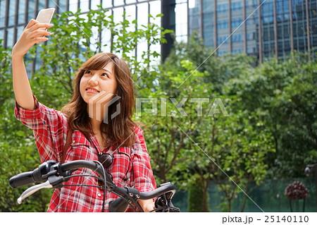 自転車に乗ってスマホで自撮りをする若い日本人の女性 25140110