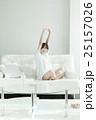 ソファに座って伸びをする女性 25157026