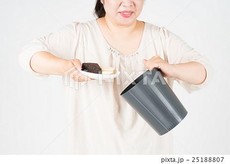ケーキをゴミ箱に捨てる太った女性 25188807