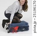キャリーバッグに荷物を詰め込む若い女性 25196170