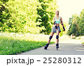 happy young woman in rollerblades riding outdoors 25280312
