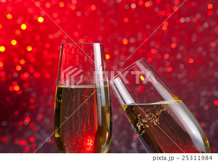 two champagne flutes with gold bubbles on red light bokeh backgroundの写真素材 [25311984] - PIXTA
