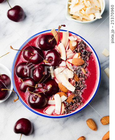 Smoothie bowl with black cherries, coconut flakes 25370960