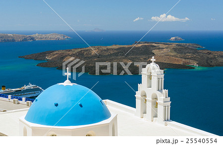 Blue-domed chapel with ochre bell tower in Oia 25540554