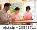 介護施設のリクエーションルームで折り紙を楽しむ高齢者と若い介護職員 25541711