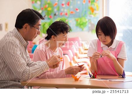 介護施設のリクエーションルームで折り紙を楽しむお年寄り二人と若い介護職員 25541713