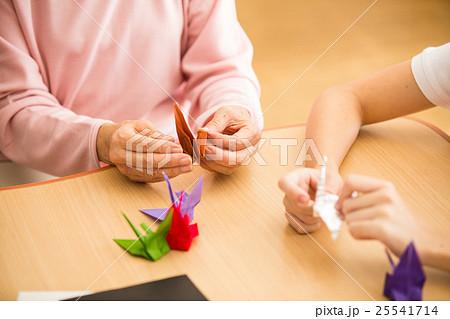 介護施設のリクエーションルームで折り紙を楽しむお年寄りと若い介護職員 25541714