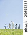 草原で紙飛行機を飛ばす小学生と先生 25655235