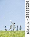 草原で紙飛行機を飛ばす小学生と先生 25655236