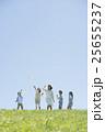 草原で紙飛行機を飛ばす小学生と先生 25655237