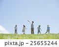 草原で紙飛行機を飛ばす小学生と先生 25655244