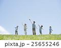 草原で紙飛行機を飛ばす小学生と先生 25655246