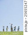 草原で紙飛行機を飛ばす小学生と先生 25655247