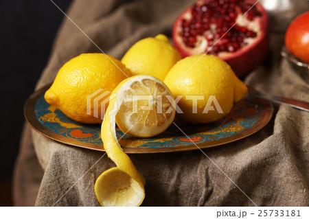 Beautiful lemons on a plate, one cut skin. 25733181