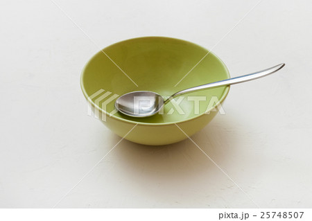 green bowl with spoon on white plasterの写真素材 [25748507] - PIXTA