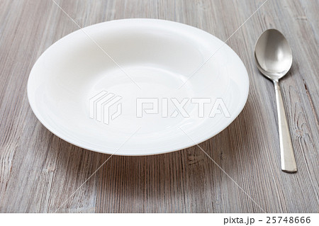 white deep plate and spoon on gray brown boardの写真素材 [25748666] - PIXTA