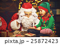 Santa Claus and a elf child in a Christmas working, reading lett 25872423