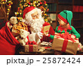 Santa Claus and a elf child in a Christmas working, reading lett 25872424