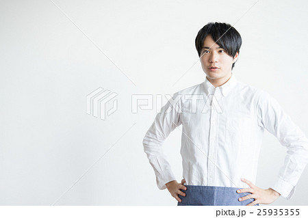 腰に手を当てる飲食店の男性(カフェ・従業員・爽やか) 25935355