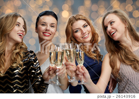 happy women clinking champagne glasses over lightsの写真素材 [26143916] - PIXTA