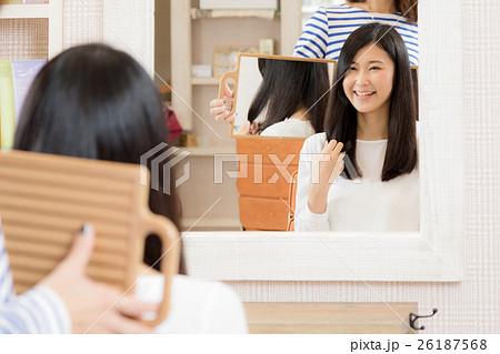 美容院で髪を切る女性 ヘアサロン 鏡 仕上がりの写真素材