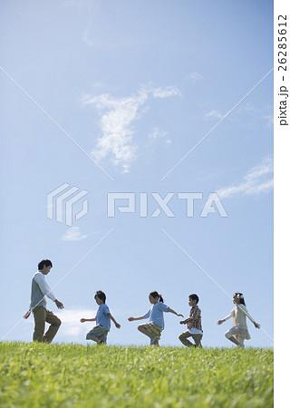 草原を歩く小学生と先生 26285612