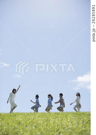 草原を歩く小学生と先生 26285891