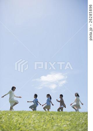 草原を歩く小学生と先生 26285896