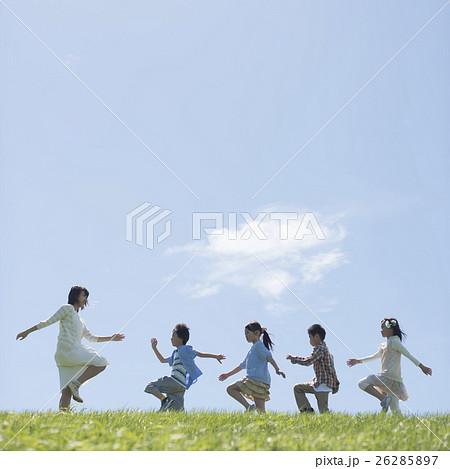 草原を歩く小学生と先生 26285897