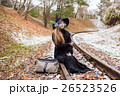 Young woman smoking a cigarette sitting on tracks 26523526