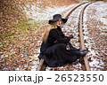Young woman smoking a cigarette sitting on tracks 26523550