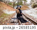 Young woman smoking a cigarette sitting on tracks 26585195