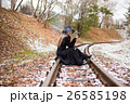Young woman smoking a cigarette sitting on tracks 26585198