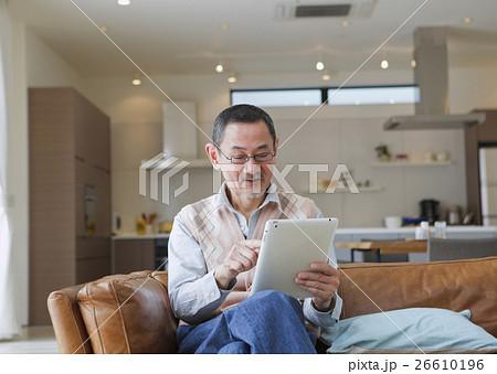 ソファでタブレットPCを操作するシニアの男性 26610196
