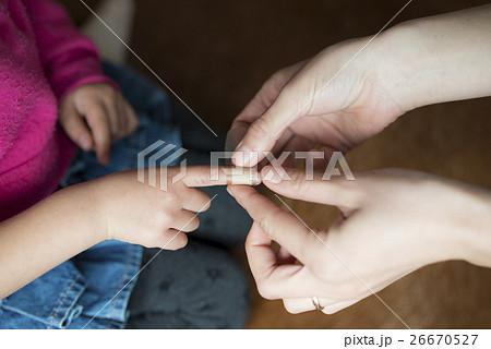 子供の指先に絆創膏を貼る母の手 26670527