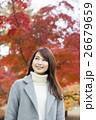 奈良県奈良市の奈良公園の紅葉を背景にしている笑顔の若い女性 26679659