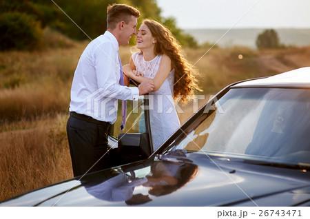 bride and groom kissing near car on wedding walk 26743471