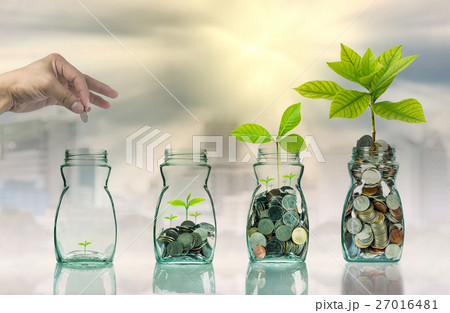 Hand putting mix coins and seed in clear bottle on cityscape photo blurred cityscape background,Business investment growth conceptの写真素材 [27016481] - PIXTA
