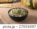 Green pumpkin seeds peeled in a black cup 27054097