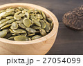Close-up green pumpkin seeds in a wooden cup 27054099