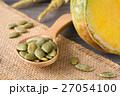 Green pumpkin seeds in a wooden spoon 27054100