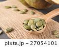 Green pumpkin seeds in a wooden spoon 27054101