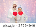 smiling couple in winter clothes with red hearts 27294949