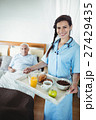 Nurse serving breakfast to senior man 27429435