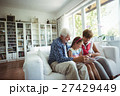 Grandparents and granddaughter looking at photo album in living room 27429449